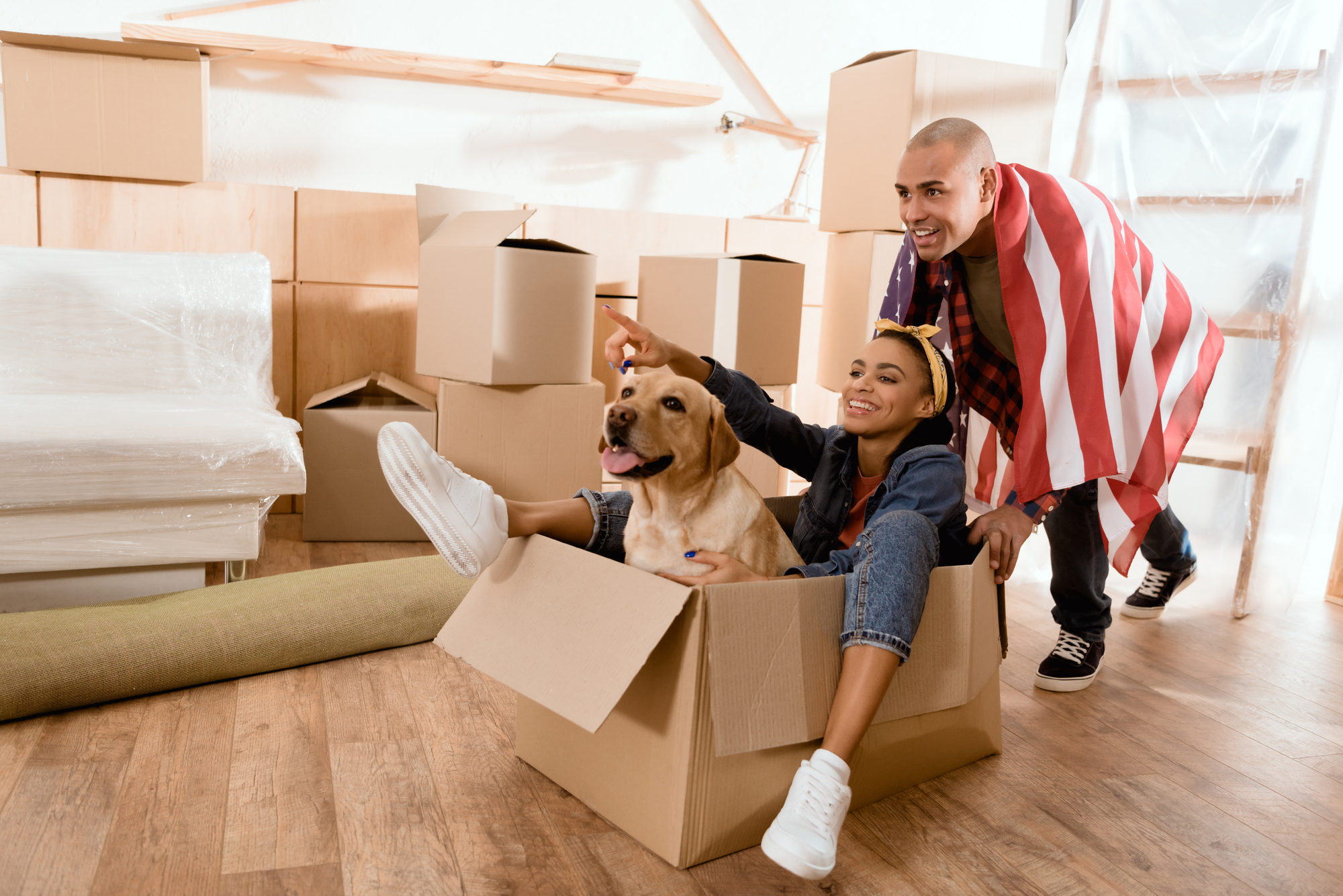 African american couple having fun with dog in new apartment