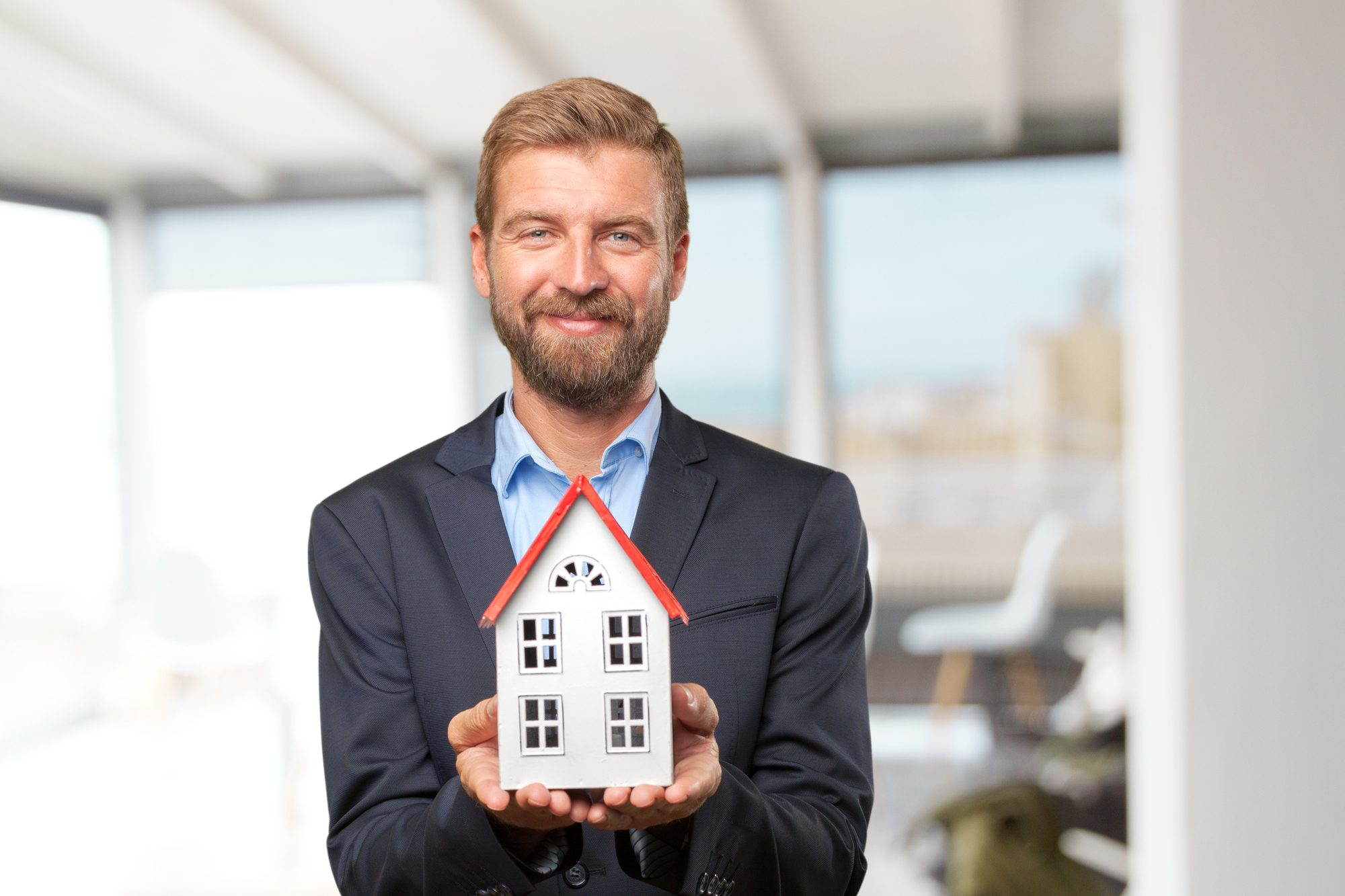 Blond businessman with toy house