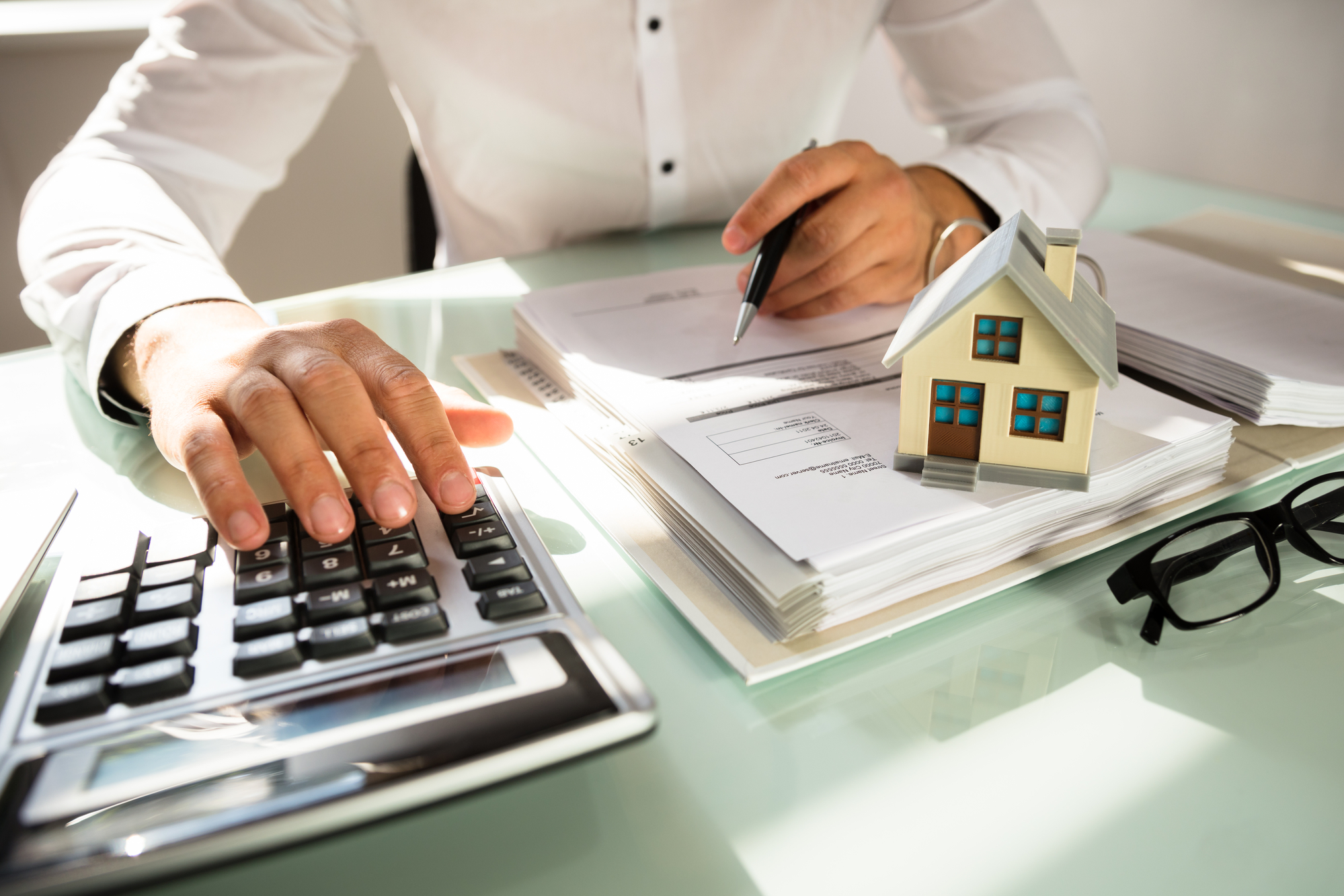 Businessmans hand calculating invoice with house model in office