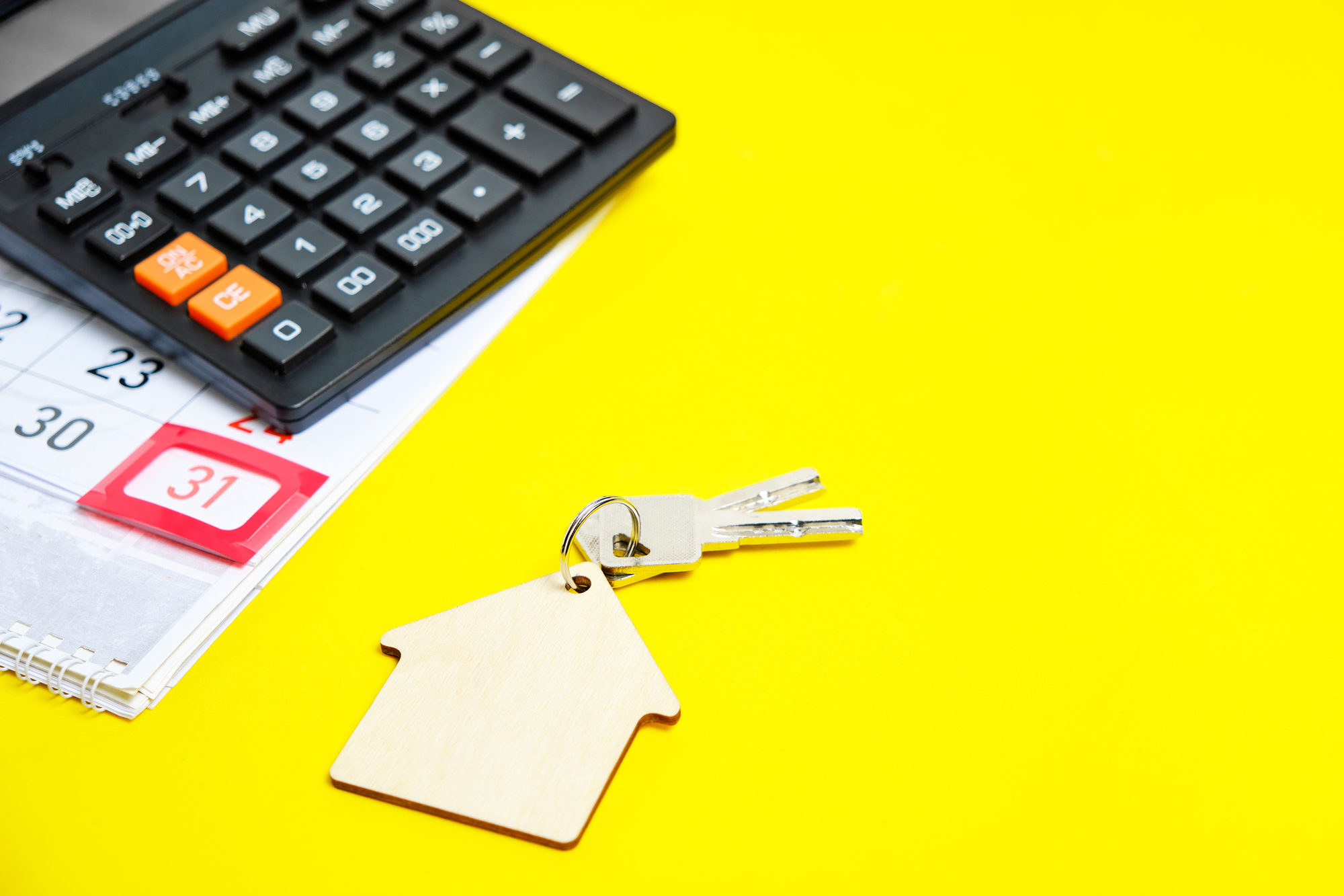 Calendar End of the Month Calculator Keys to a House or Apartment on a Yellow Background Concept Buying an Apartment House New Year Gift