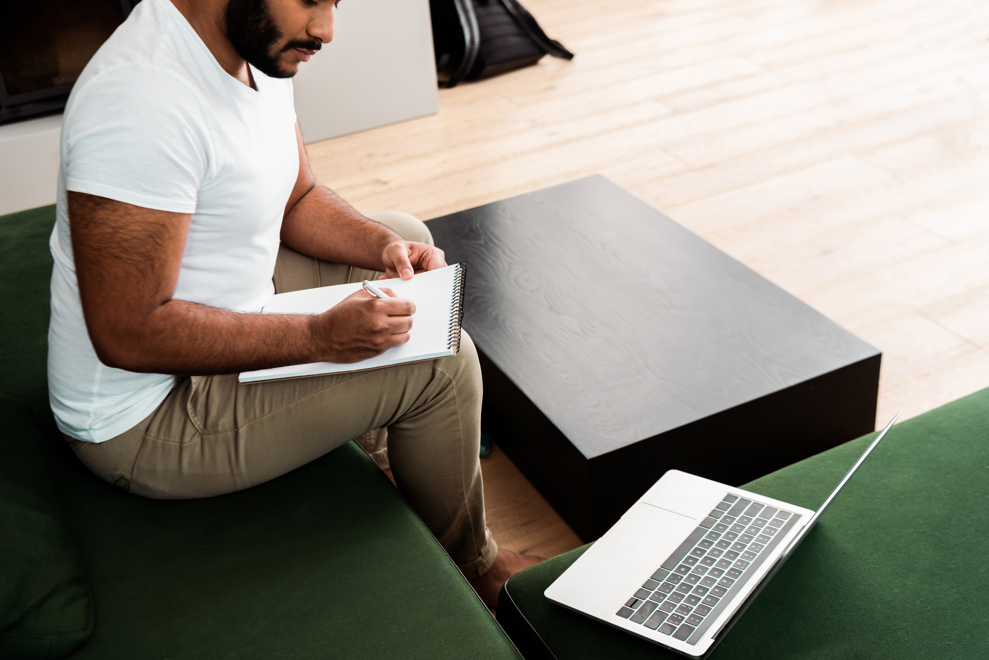 Cropped view of bearded african american man writing in notebook near laptop, study online