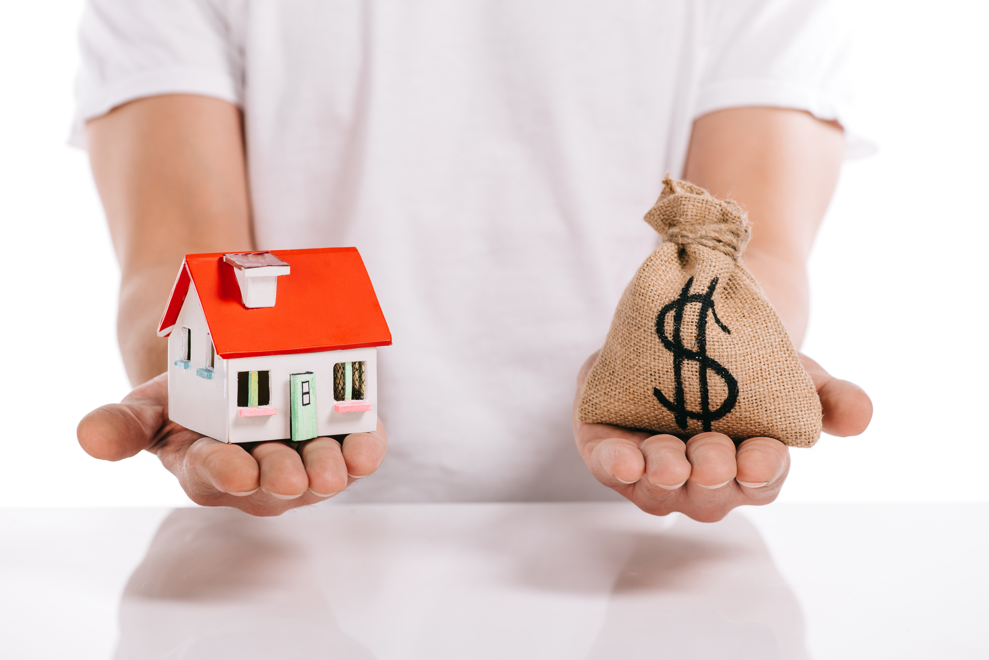 Cropped view of man holding house model and moneybag isolated on white, mortgage concept