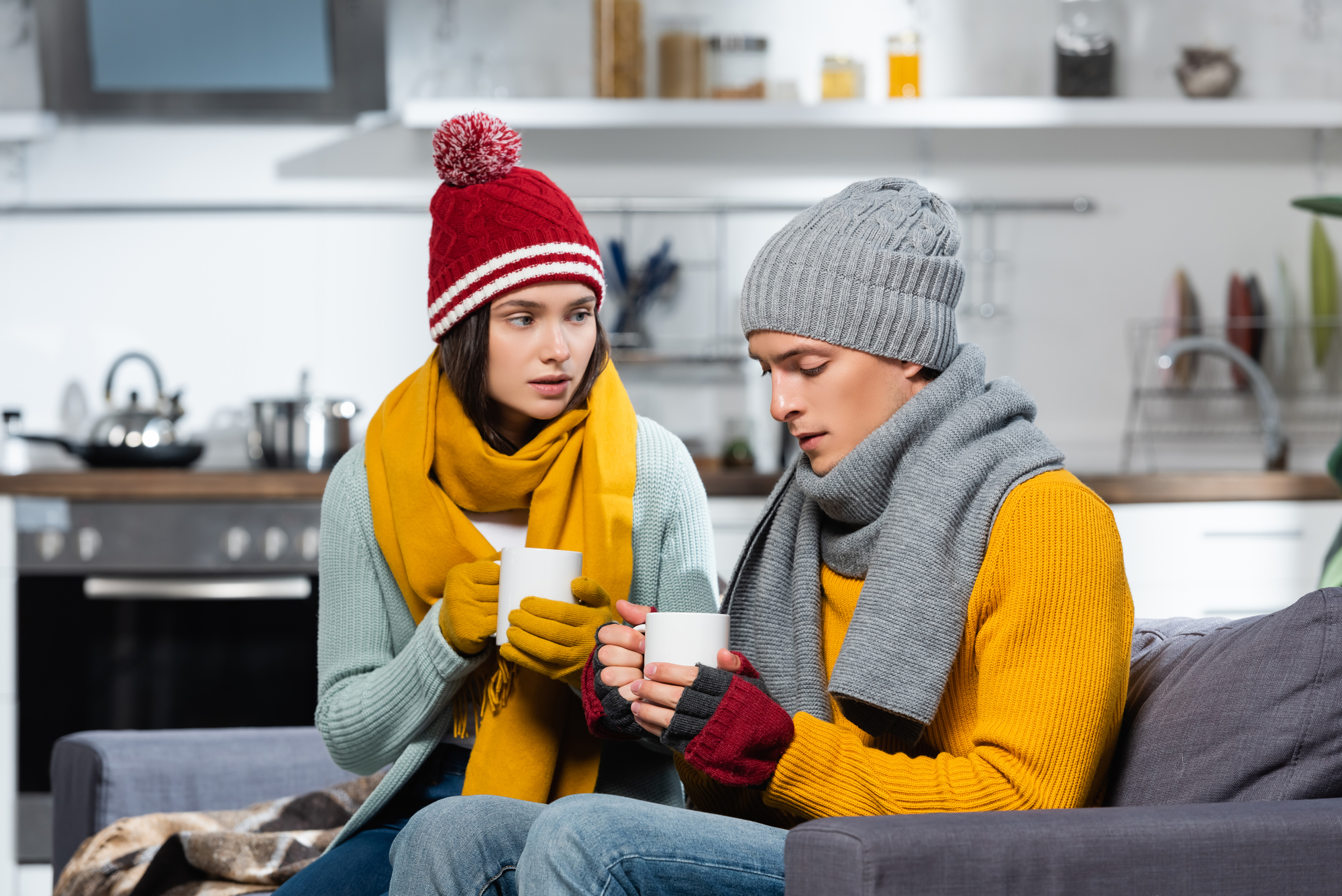 Freezing couple in knitted hats, scarfs and gloves holding cups of warming beverage in cold kitchen