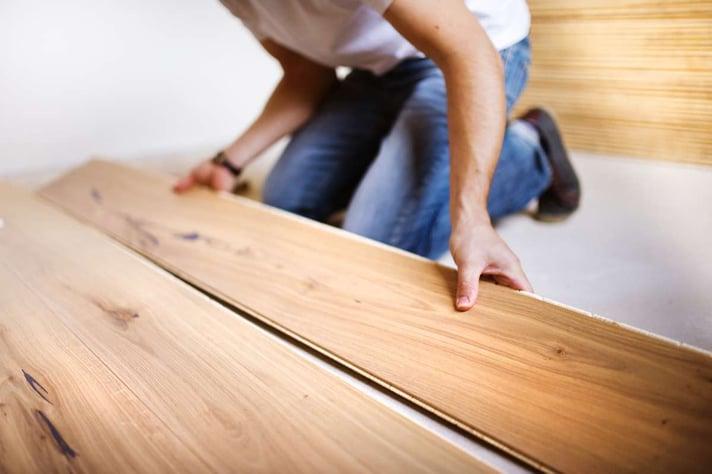Handyman installing wooden floor (R) (S)