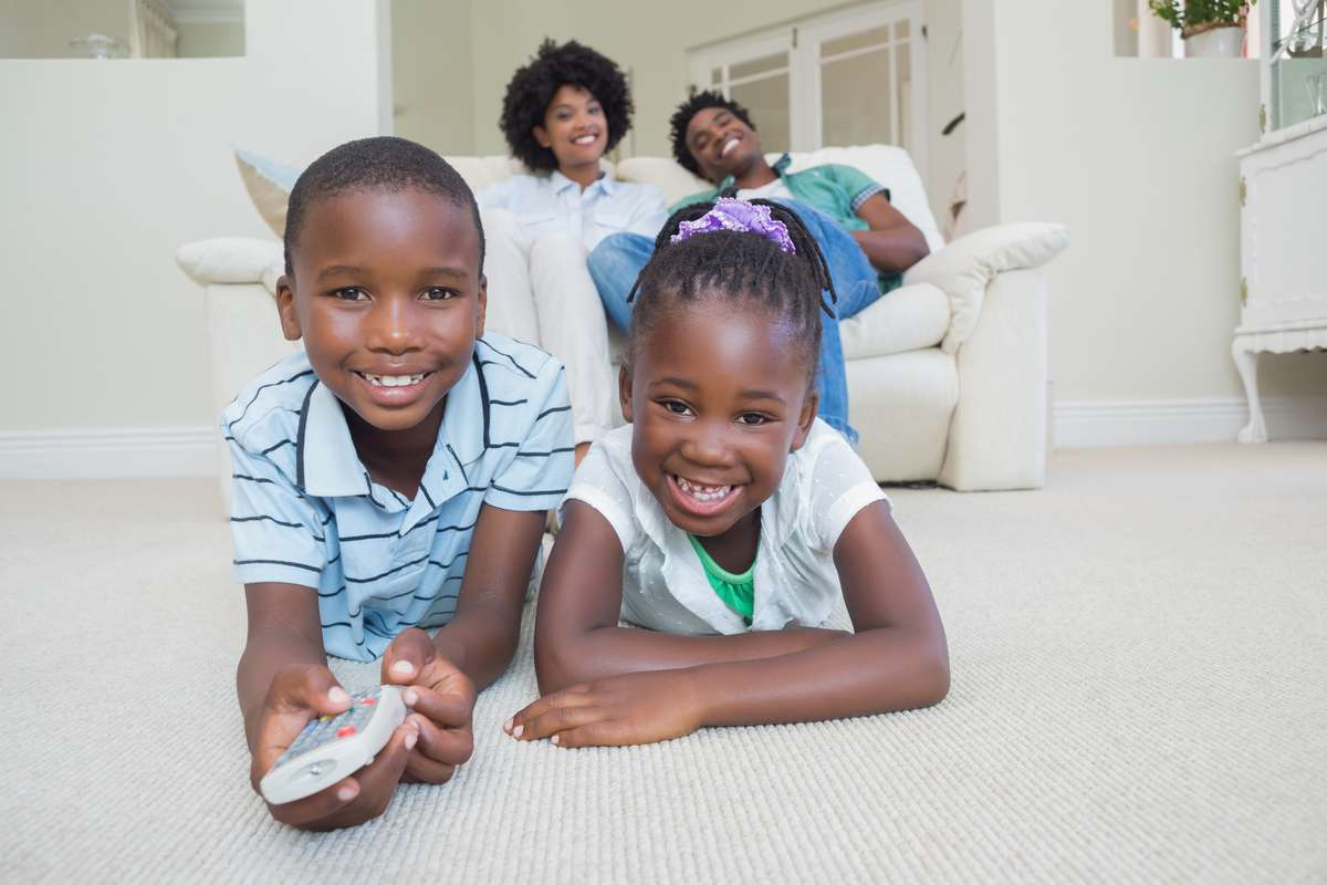 Happy siblings lying on the floor watching tv (R) (S)