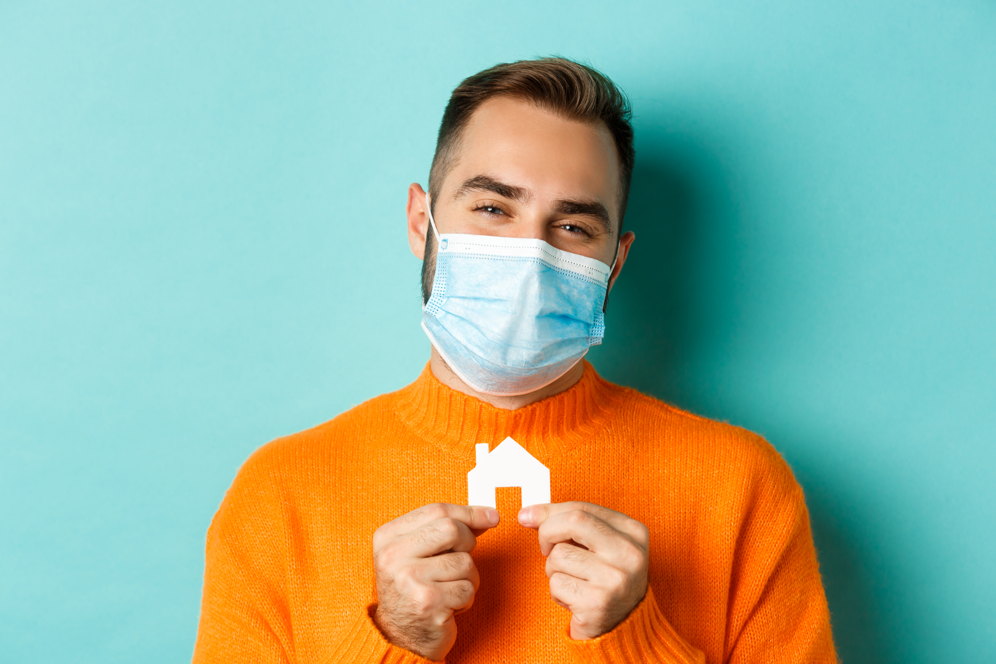 Real estate and coronavirus pandemic. Close-up of adult man in medical mask holding small paper house maket and smiling, searching for apartment