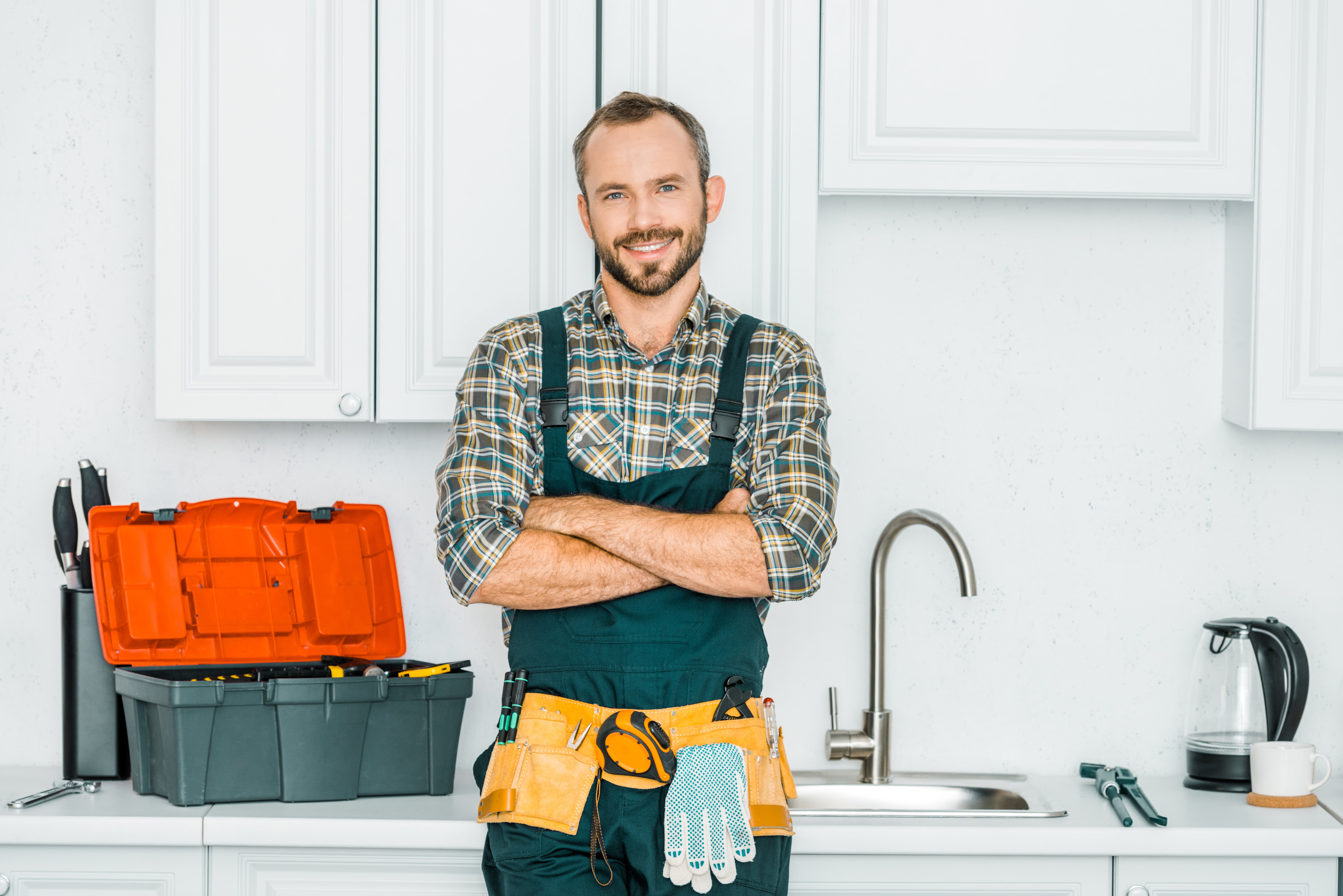 Smiling handsome plumber standing with crossed arms