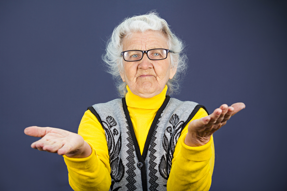 Closeup portrait, clueless senior, mature, elderly woman, arms out asking why whats problem who cares so what I dont know, isolated blue background. Negative human emotion, facial expression feeling