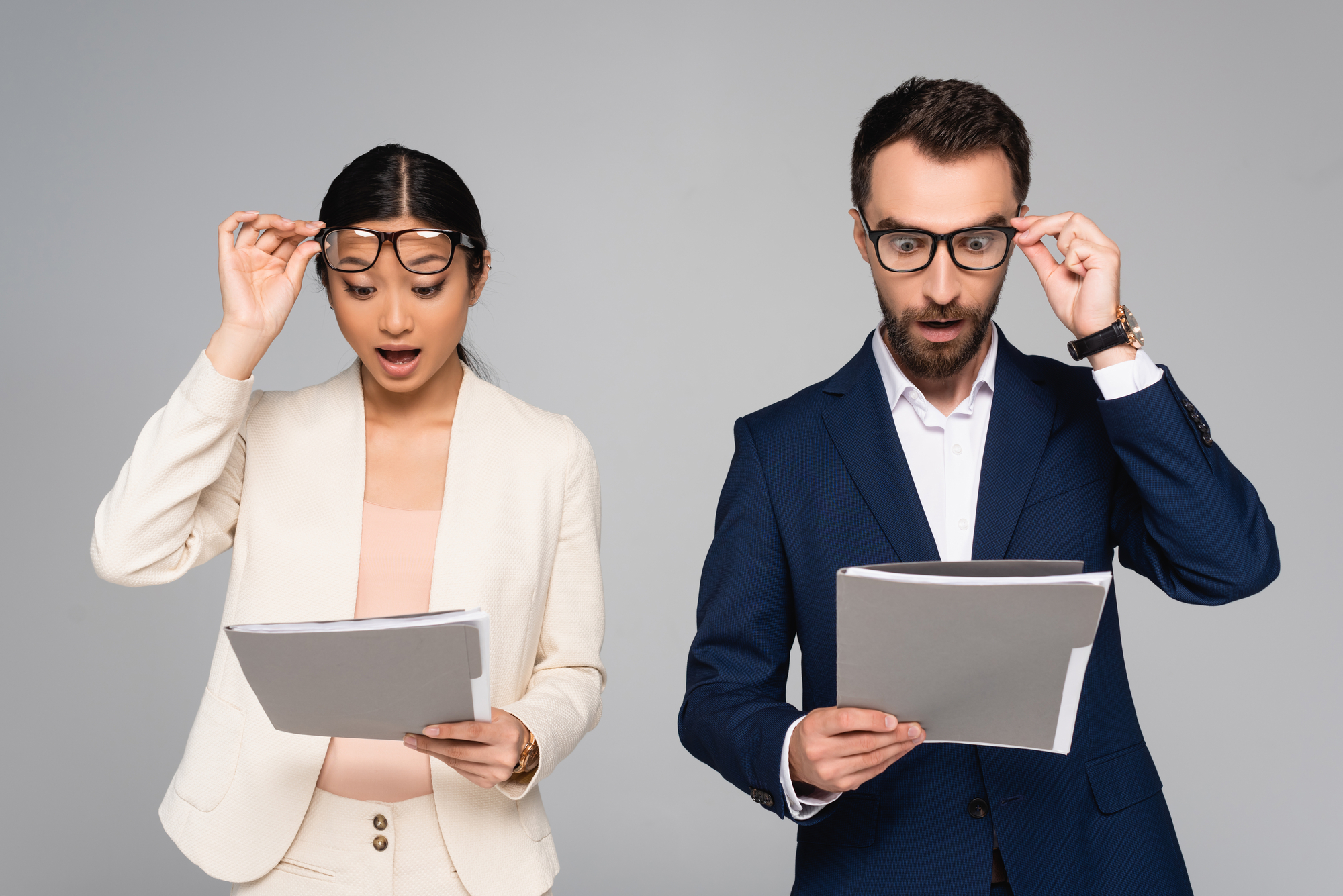 Surprised interracial business partners looking at documents and touching eyeglasses isolated on grey