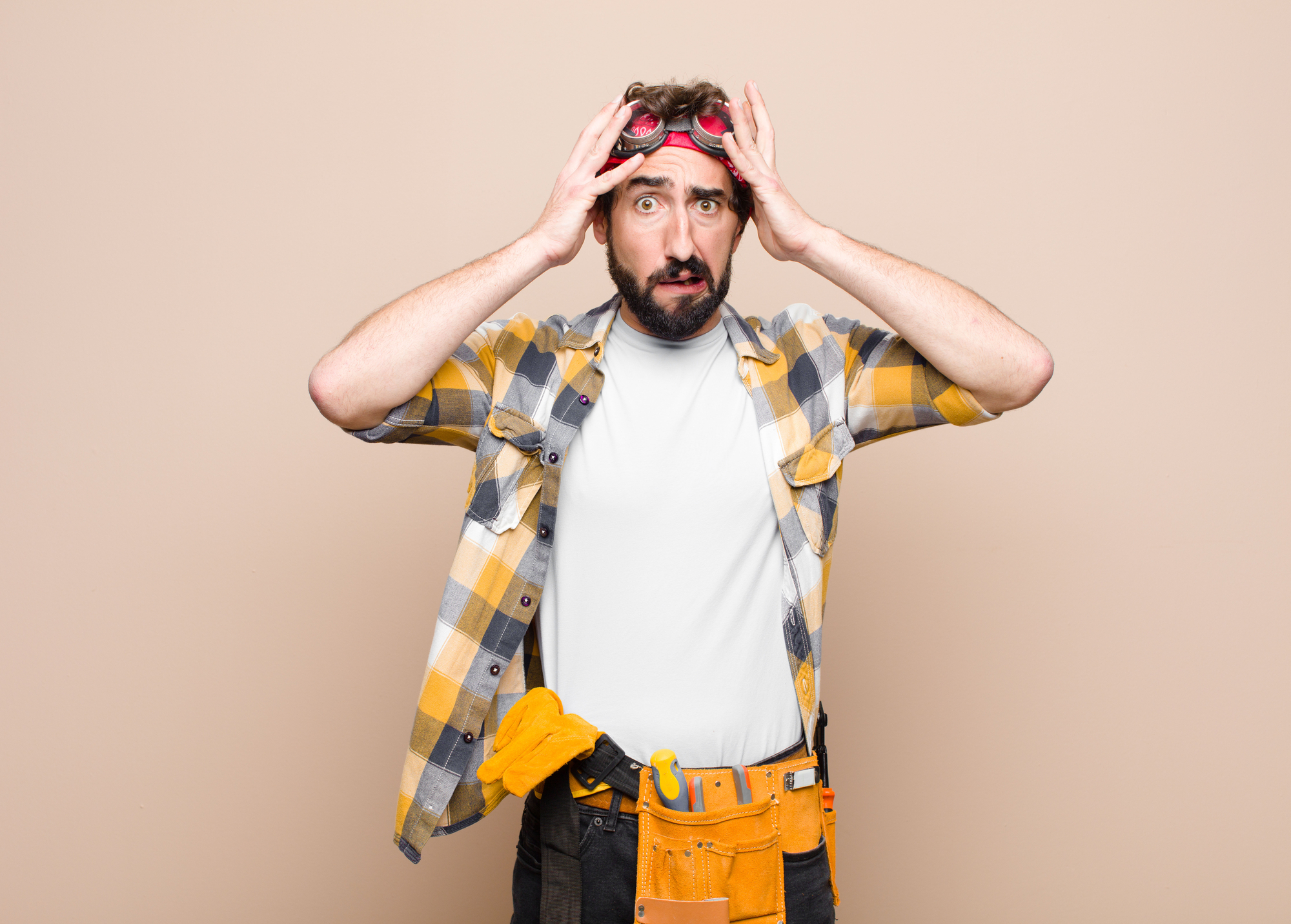 Young housekeeper man feeling horrified and shocked, raising hands to head and panicking at a mistake against flat wall